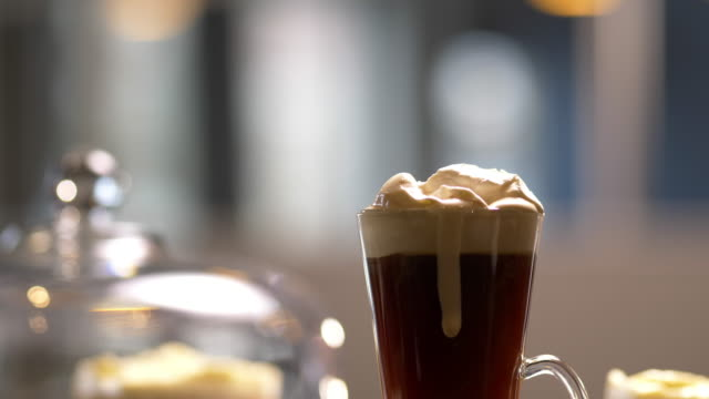 coffee drink with whipped cream dripping down side of hot glass mug. - 温かい飲み物点の映像素材/bロール