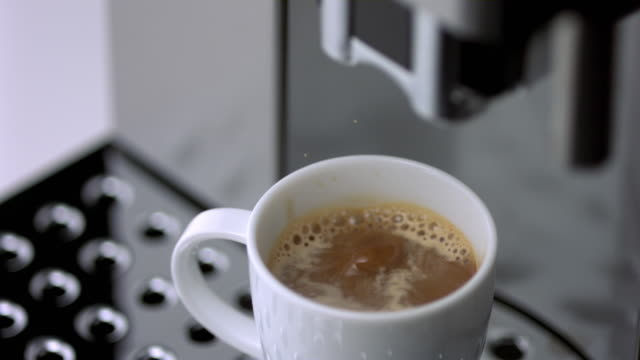 SLO MO CU SELECTIVE FOCUS Coffee dripping from espresso machine into cup