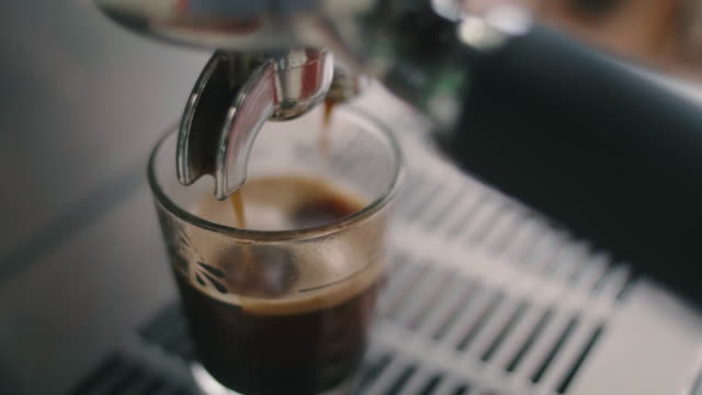 vídeos de stock e filmes b-roll de coffee dripping from machine into cup. - pequeno almoço