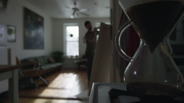 SLO MO. Coffee drips into coffee pot as young artist paints on large canvas in city apartment.