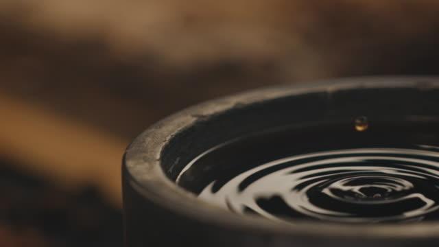 stockvideo's en b-roll-footage met koffie druppel vallend in container in fabriek - koffie drank