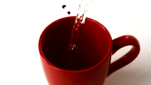 Coffee granules and water going into red mug