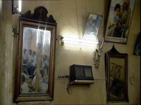 Coffee house wall with paintings and mirror reflecting men sitting at tables / Baghdad Iraq