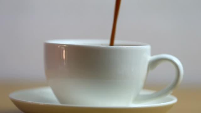 kaffe hälls i en vit glas och med en sked i rör om väl.