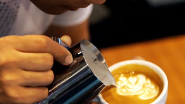 coffee latte art, milk pouring by a barista. - latte stock videos and b-roll footage