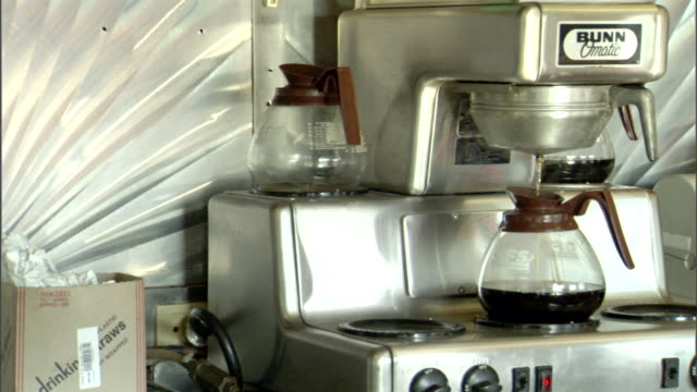 coffee machine filling up coffee pot on machine in unidentifiable diner breakfast espresso black coffee morning caffeine caffeinated - caffeine stock videos & royalty-free footage