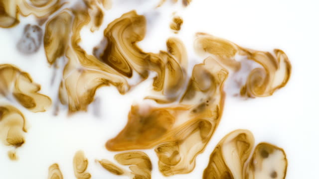 Coffee mixing with milk. Slow motion