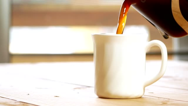 coffee pouring into a white cup and hand stirring the coffee on wooden table - tazza da caffè video stock e b–roll
