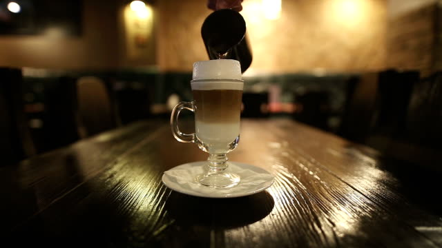 coffee pouring into mug with cream, slow motion - cafe macchiato stock videos and b-roll footage