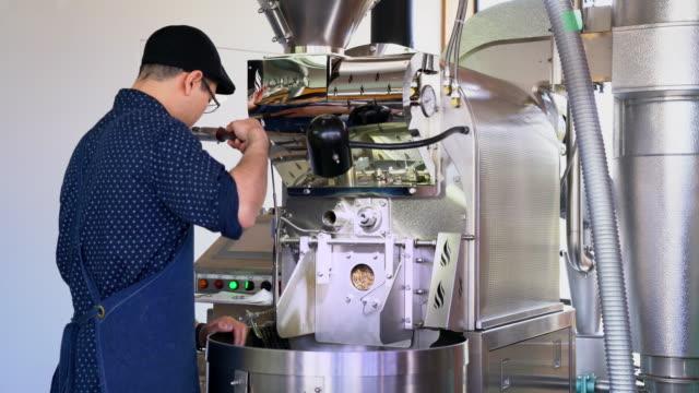 その進捗状況をチェックするため豆の臭いがするコーヒーの焙焼 - 作業場点の映像素材/bロール