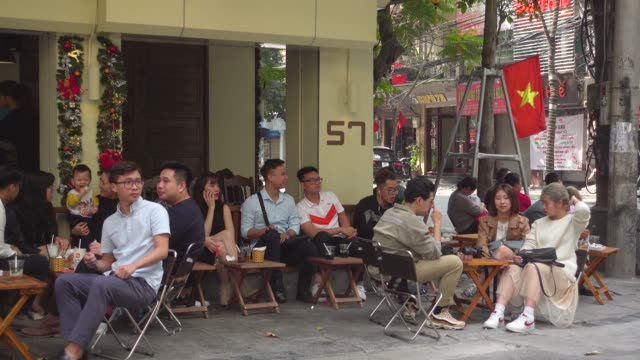 coffee shop at hanoi full of young people during tet. hoan kiem old district quarter. vietnamese national red flag with iconic yellow star - newly industrialized country stock videos and b-roll footage