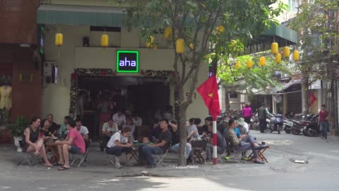 coffee shop at hanoi full of young people during tet. hoan kiem old district quarter. vietnamese national red flag with iconic yellow star - establishing shot bildbanksvideor och videomaterial från bakom kulisserna