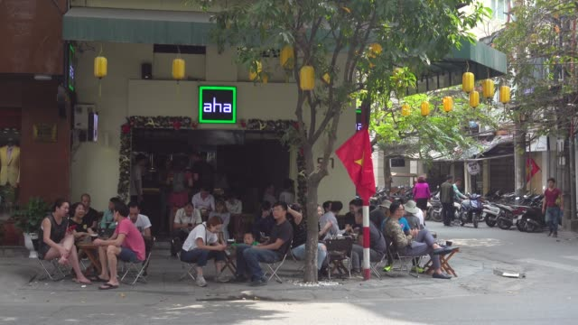 coffee shop at hanoi full of young people during tet. hoan kiem old district quarter. vietnamese national red flag with iconic yellow star - etablera scenen bildbanksvideor och videomaterial från bakom kulisserna