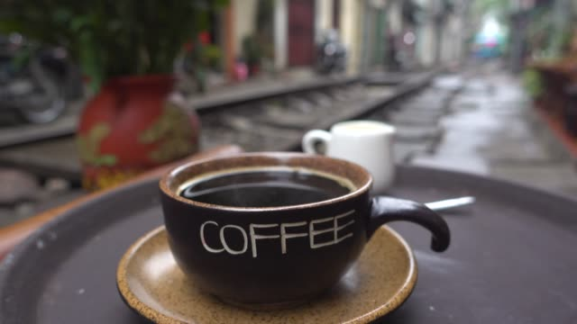 coffee shop at hanoi train street. close up. iconic image of narrow street with the railway in the middle of the buildings - traditionally vietnamese stock videos & royalty-free footage