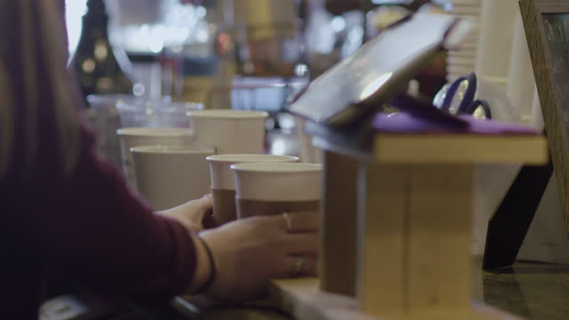 CU. Coffee shop barista fixes to go cups and rings up order on tablet computer.