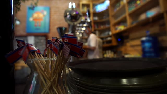 coffee shop in hanoi displaying north korean and american flags for the summit with donald trump and kim jongun - summit meeting stock videos and b-roll footage