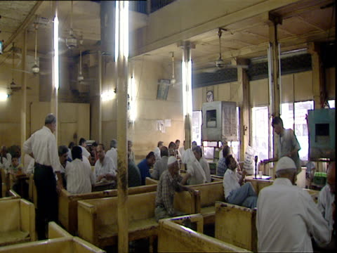 coffee shop interior men with skullcaps sitting on wooden benches fans whirring overhead / baghdad iraq - ceiling fan stock videos & royalty-free footage