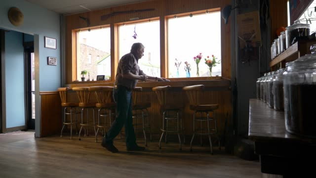 coffee shop owner arranging stools before the shop opens. - owner stock videos & royalty-free footage