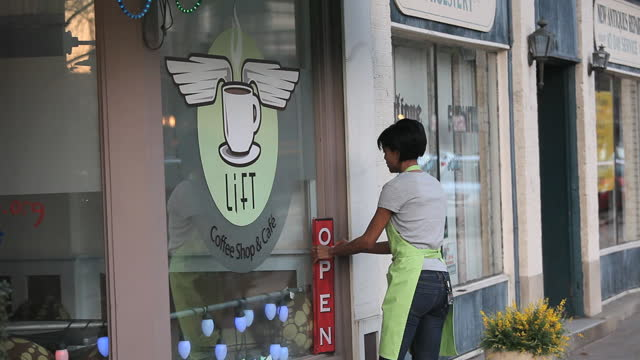 Coffee shop owner in apron placing 'Open' sign in front of cafe and looking up and down street in anticipation with arms crossed