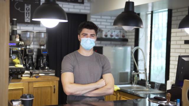 stockvideo's en b-roll-footage met coffeeshophouder poseren tijdens covid-19 pandemie - kleinhandel