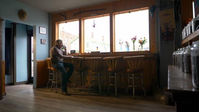 vídeos de stock, filmes e b-roll de coffee shop owner waiting for business before the shop opens. - localidade pequena