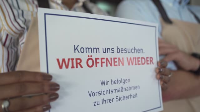 coffee shop worker holding an information sign on german language about reopening and safety measurements in coffee shop - information sign stock videos & royalty-free footage