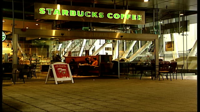 vídeos de stock, filmes e b-roll de central london int general views starbucks coffee shop starbucks sign 'the red cups are coming' various shots of people mostly businessmen and women... - starbucks