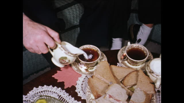 vidéos et rushes de 1955 montage coffee table, man pouring milk and sugar into coffee, tea sandwiches / toronto, canada - thé boisson chaude