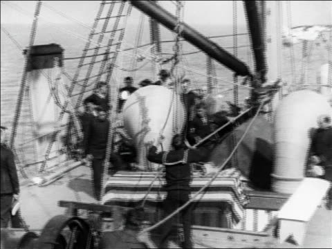 coffin draped with us flag being lifted by rope from ship's hold / newsreel - anno 1925 video stock e b–roll
