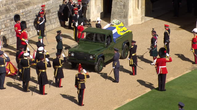 coffin of prince philip, duke of edinburgh, laid on land rover hearse, in grounds of windsor castle, for funeral, royal family stand behind the hearse - carefree stock videos & royalty-free footage