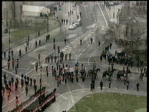 vídeos de stock e filmes b-roll de coffin of queen mother carried from westminster hall / crowds / coffin placed on gun carriage / members of the royal family walking behind coffin /... - 2002