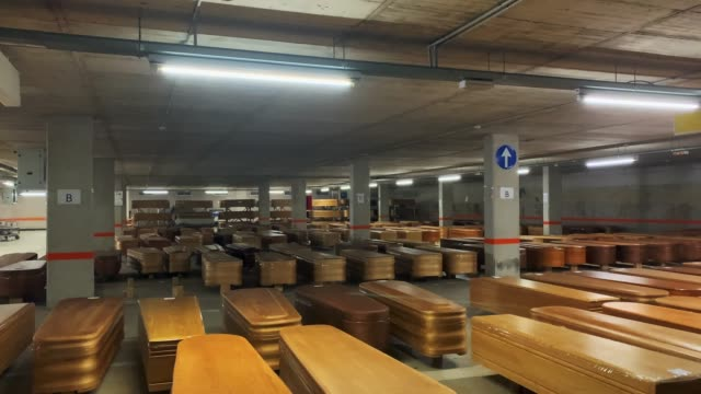 vídeos y material grabado en eventos de stock de coffins containing the bodies of people who have died of coronavirus are lined up in the long-term parking of the collserola morgue before they... - ataúd