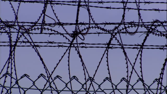 coiled barbed wire tops a security fence. - bestrafung stock-videos und b-roll-filmmaterial
