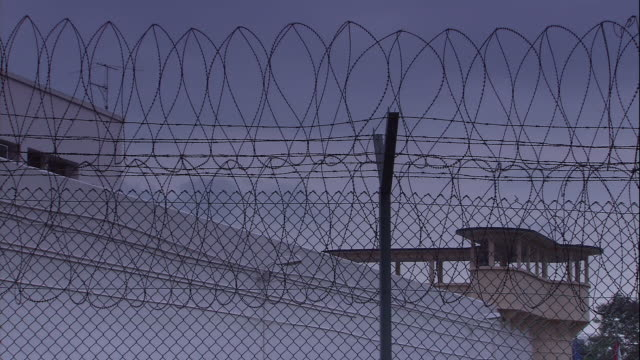 coiled barbed wire tops security fences around a guard tower in singapore. - law stock videos & royalty-free footage