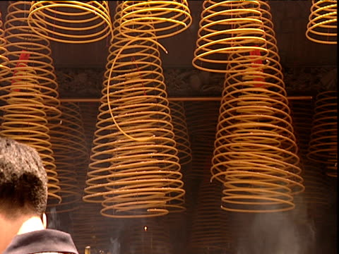stockvideo's en b-roll-footage met coils of burning incense hanging people pass by hong kong - gelovige