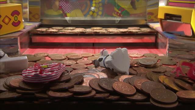 coin pusher at a seaside amusements arcade - geldmünze stock-videos und b-roll-filmmaterial