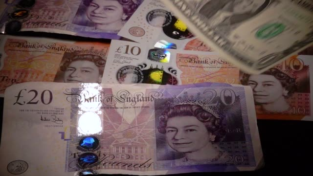 £1 coins are seen with the new £10 note on october 13 2017 in bath england currency experts have warned that as the uncertainty surrounding brexit... - valuta britannica video stock e b–roll