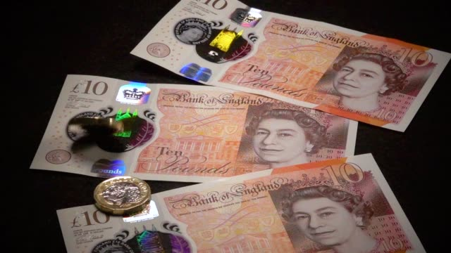 £1 coins are seen with the new £10 note on october 13 2017 in bath england currency experts have warned that as the uncertainty surrounding brexit... - banknote stock videos & royalty-free footage