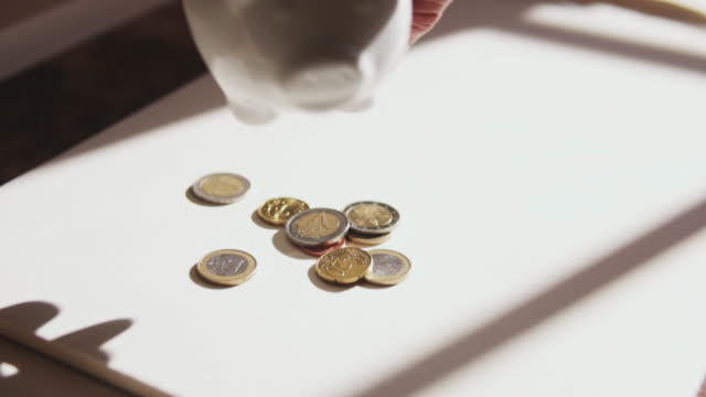 coins falling out a piggy bank. - european union coin stock videos & royalty-free footage