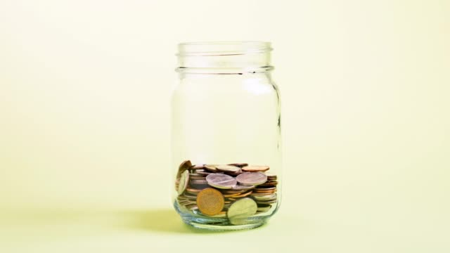 coins in a jar - savings stock videos & royalty-free footage