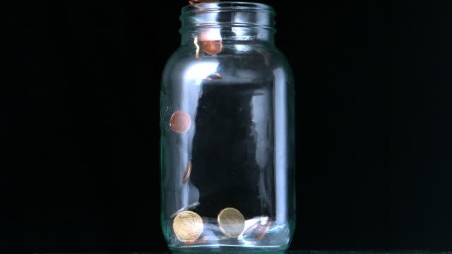 coins pouring into glass jar - geldmünze stock-videos und b-roll-filmmaterial