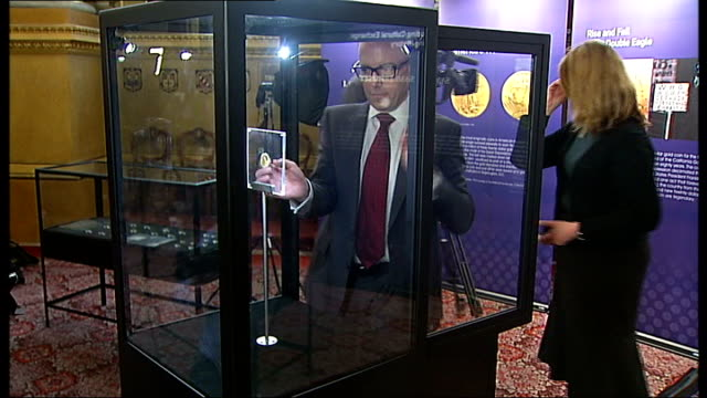 rare us double eagle coin goes on display in london; display case opened and swanson photographed with coin / us double eagle coin - us coin stock videos & royalty-free footage
