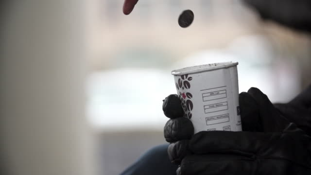 coins thrown into homeless man's cup - housing difficulties stock videos & royalty-free footage
