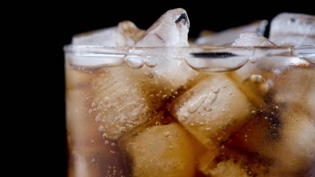 vídeos y material grabado en eventos de stock de burbujas de coca coca en vidrio con hielo - gaseosa