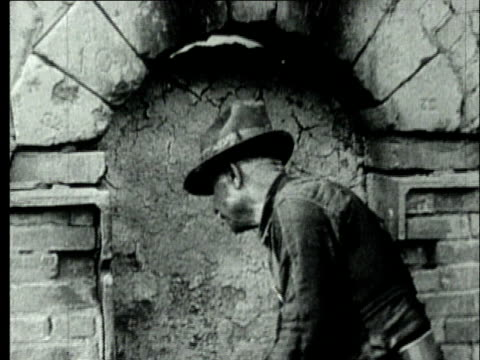 1927 b/w ms coke oven worker sealing brick oven door with mud material in preparation for 'coking' process/ pennsylvania, usa - ziegel stock-videos und b-roll-filmmaterial