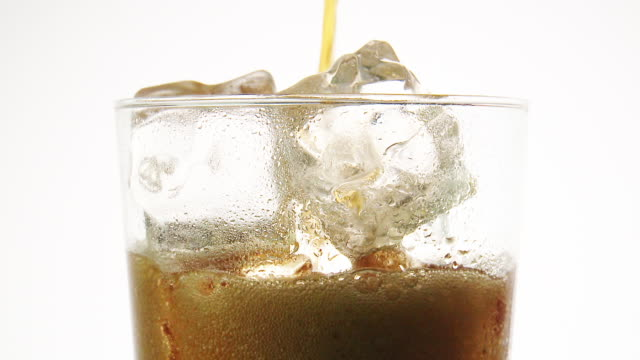 CU Cola drink pouring in glass with ice