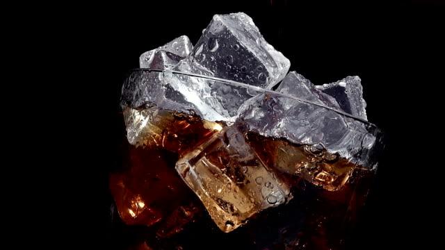 vídeos y material grabado en eventos de stock de verter cola soda en un vaso de hielo en lento movimiento sobre un fondo negro - cola gaseosa