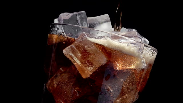 Pouring cola soda into  a glass of ice at slow motion on a black background
