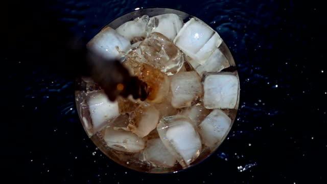 gießen limonade in glas cola mit eis mit akzenten in zeitlupe - cola stock-videos und b-roll-filmmaterial
