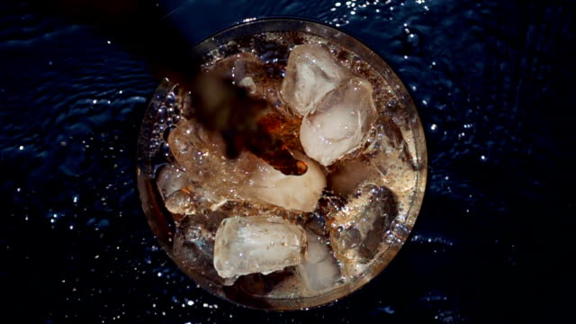 Pouring cola soda into glass of ice with splashes at slow motion